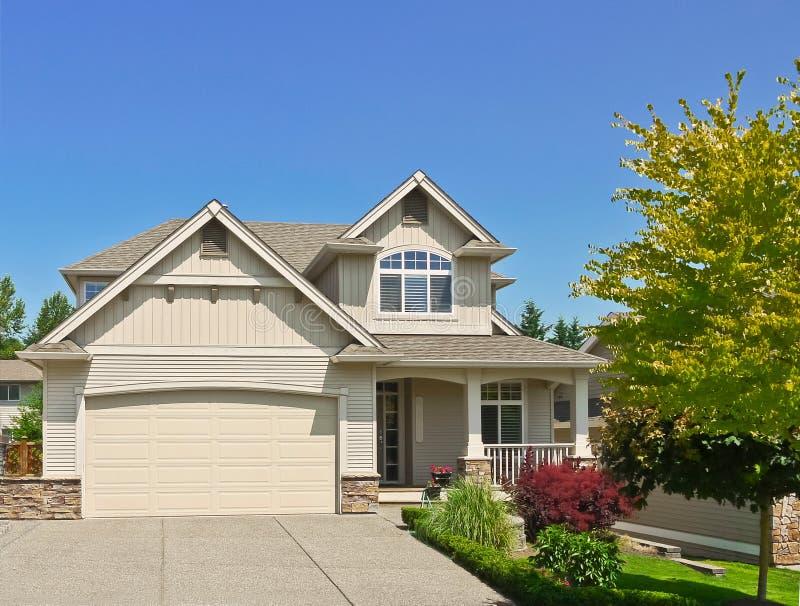 Casa nordamericana della famiglia con la strada privata concreta al garage sul fondo del cielo blu immagini stock