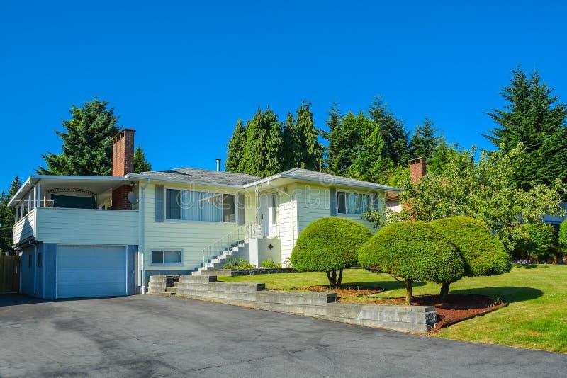 Casa nordamericana della famiglia con la strada privata e le scala dell'asfalto all'entrata fotografie stock libere da diritti