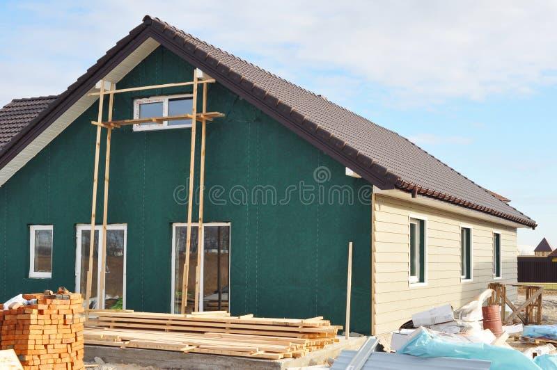 Casa nova de construção com a membrana plástica do tapume e da isolação na parede exterior da casa imagens de stock