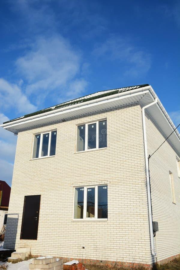 Casa nova de construção do tijolo dos tijolos brancos Porta do metal da entrada, calha do telhado, janelas fotografia de stock royalty free