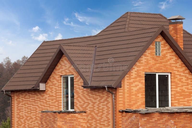 Casa nova do tijolo com chaminé modular, a telha de telhado revestida de pedra do metal, as janelas plásticas e a calha da chuva fotografia de stock royalty free