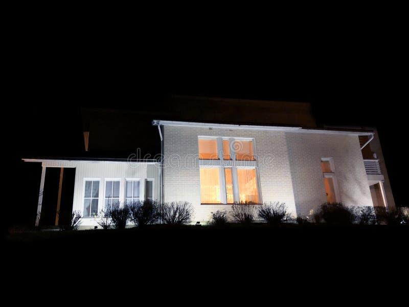 Casa nova na noite com luzes Casa moderna com garagem Luz morna acolhedor da janela Casa luxuosa no crepúsculo fotos de stock royalty free