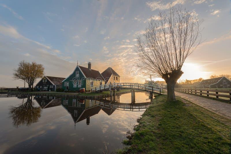 Casa olandese verde tradizionale con poco ponte di legno contro cielo blu nel villaggio di Zaanse Schans fotografia stock