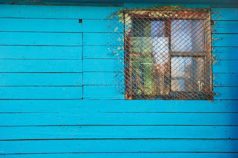 Casa ou celeiro azul de madeira velho com uma janela pequena barrada foto de stock