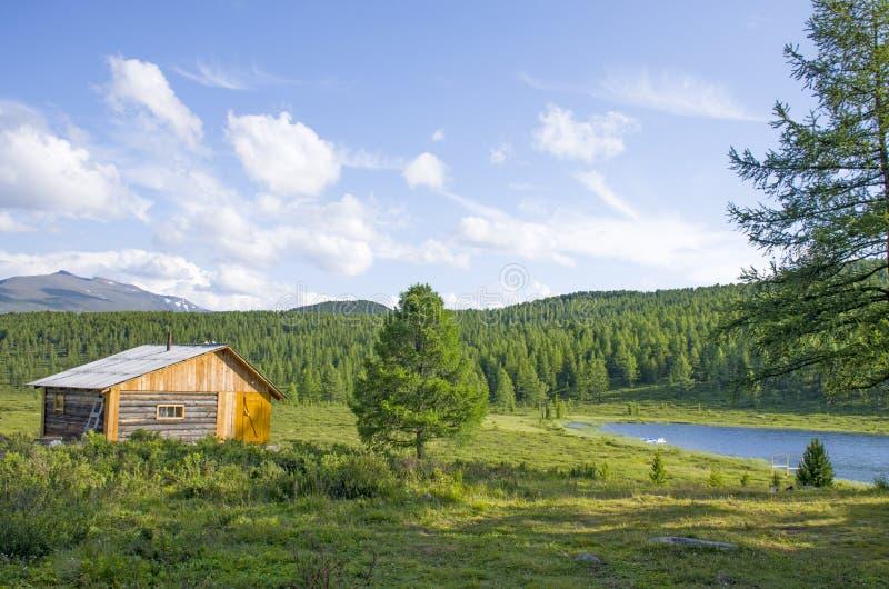 Casa para descansar em taiga contra o fundo das altas montanhas de Altai Rússia imagem de stock royalty free