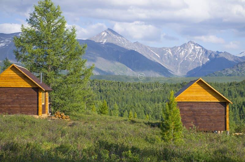 Casa para descansar em taiga contra o fundo das altas montanhas de Altai Rússia foto de stock