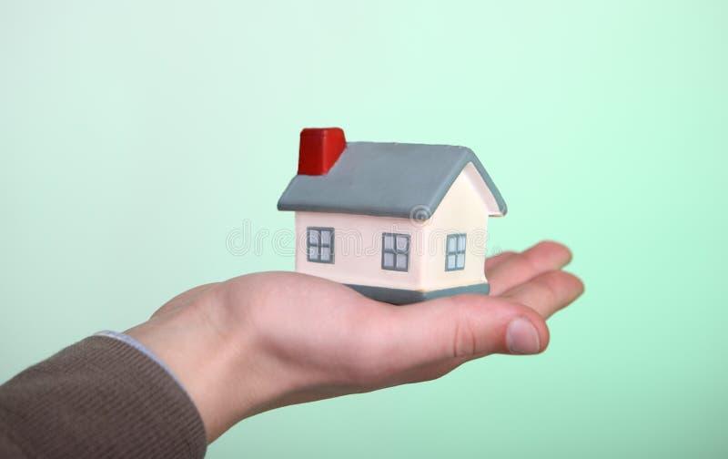Casa pequena à disposicão no fundo verde fotografia de stock