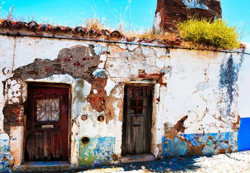 Casa pequena abandonada com Bush verde no telhado de telha vermelha velho fotografia de stock royalty free