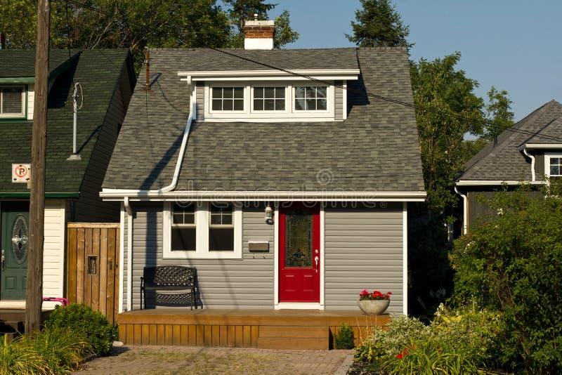 Casa pequena com porta vermelha imagem de stock