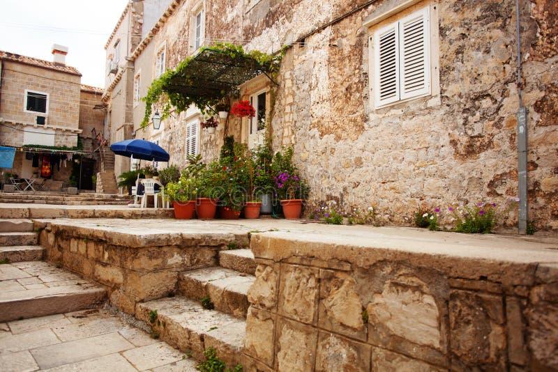 Casa pequena de encantamento com os recipientes brancos da porta da rua e do jardim do verão enchidos com as flores anuais imagens de stock royalty free