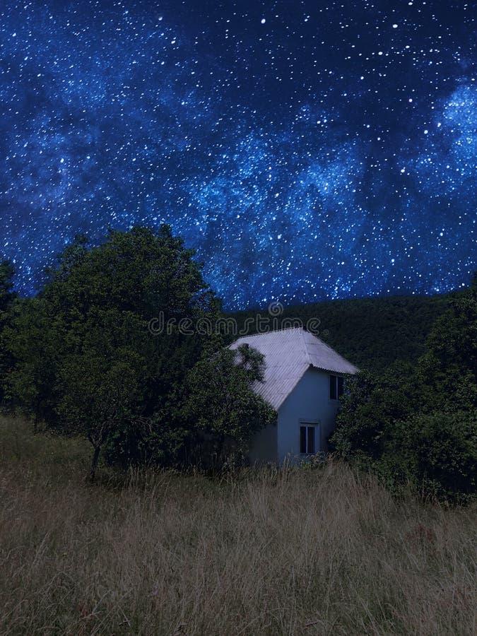 Casa pequena em uma paisagem do verão da noite com um céu estrelado bonito foto de stock