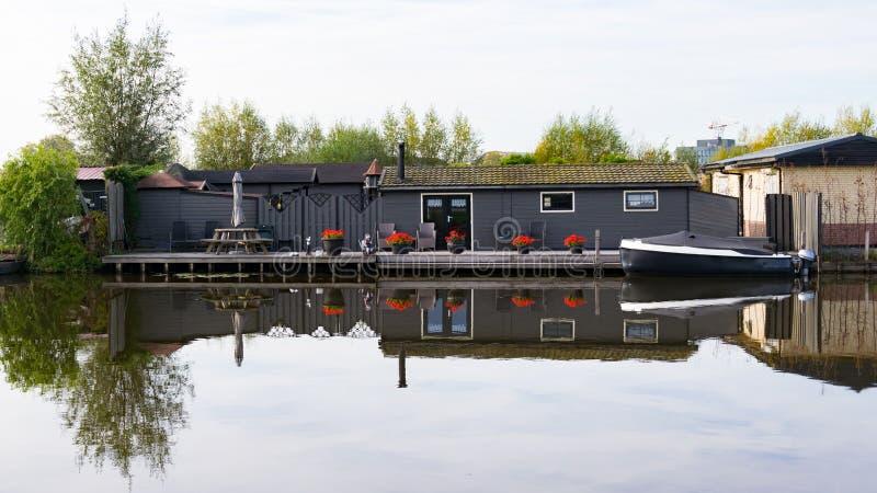 Casa pequena na água e no barco fotos de stock royalty free