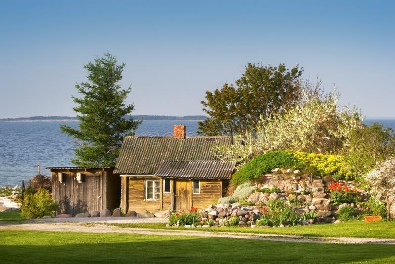 Casa pequena no beira-mar com flores de florescência foto de stock royalty free