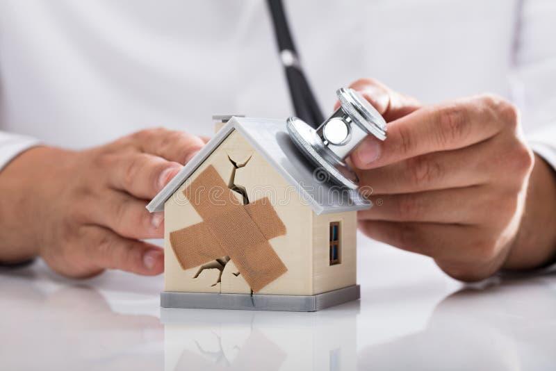 Casa quebrada de exame do doutor com estetosc?pio foto de stock