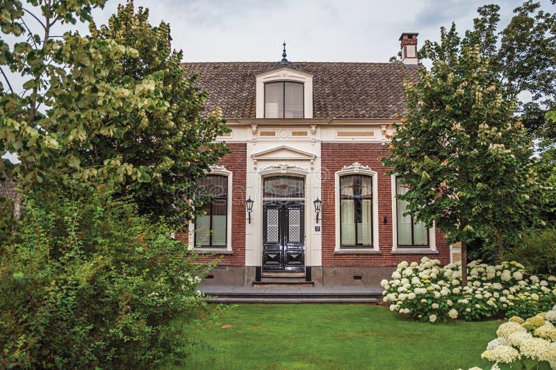 Casa rústica do tijolo encantador com jardim florescido e gramado verde em um dia nebuloso em Drimmelen fotos de stock