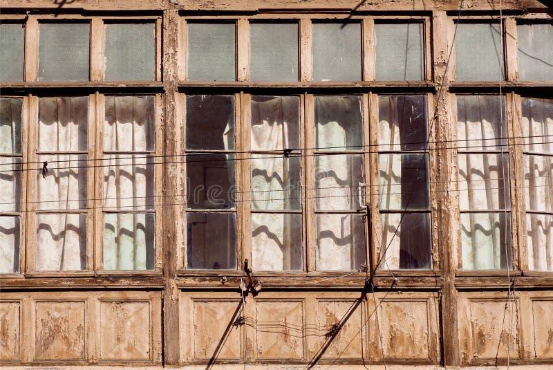 Casa rústica pobre com quadros de janelas de madeira enormes na cidade histórica foto de stock royalty free