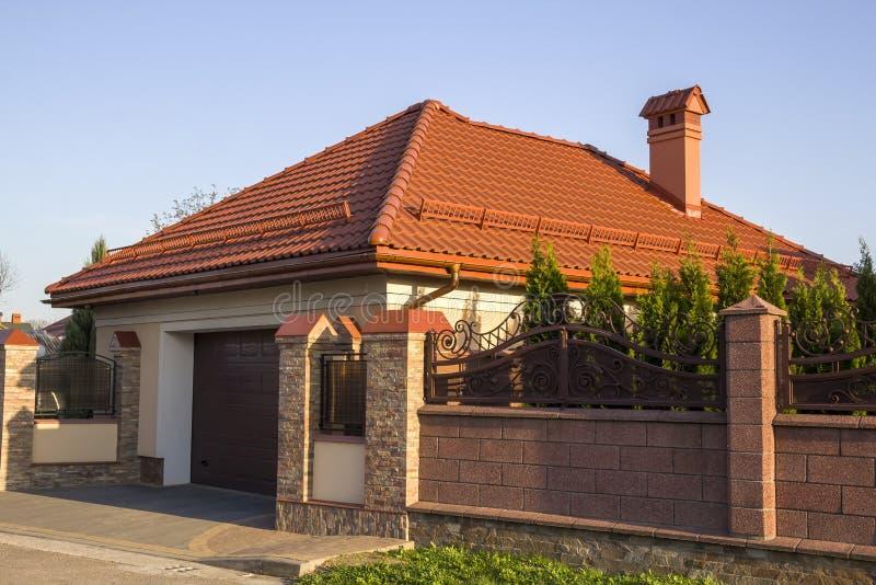 Casa residencial cara luxuoso moderna nova da casa de campo com telhado da telha, garagem e as árvores verdes na jarda atrás da c fotos de stock royalty free