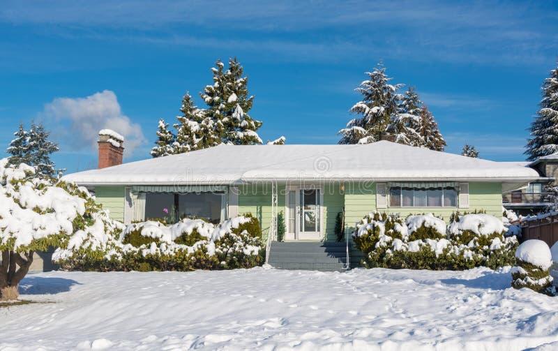 Casa residencial da família com jardim da frente na neve no dia ensolarado do inverno imagem de stock royalty free