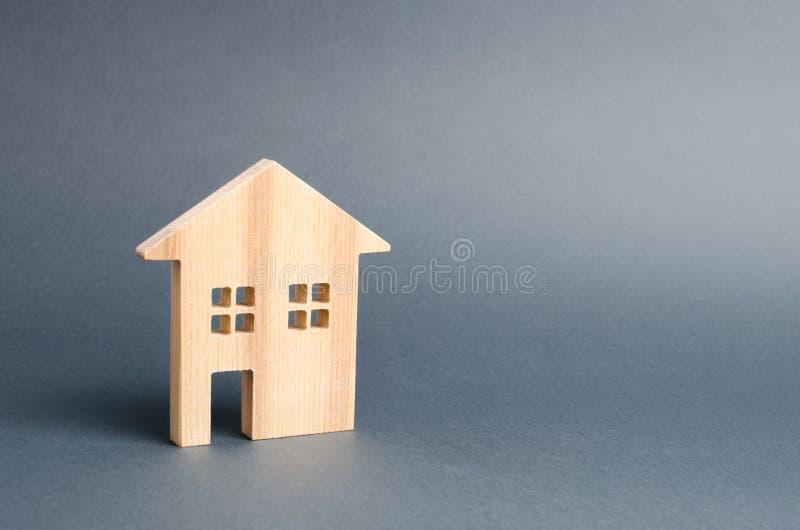 Casa residencial de madera en un fondo gris Hipoteca y cr?dito para la compra minimalism Concepto de las propiedades inmobiliaria imagen de archivo