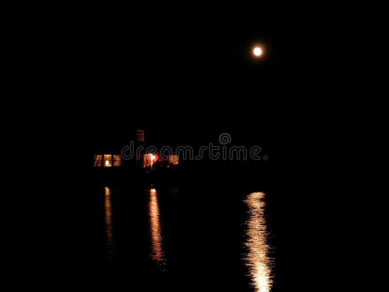 Casa riflessa in stagno alla notte fotografia stock
