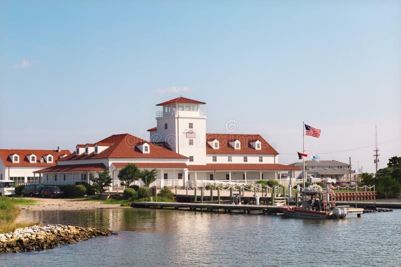 Casa roja del tejado, embarcadero de madera, barco Superficie y reflexión del agua imágenes de archivo libres de regalías