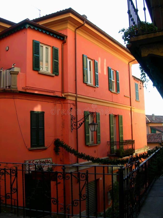 Casa roja en la calle estrecha en la aldea de Bellagio, Italia en el lago Como imagenes de archivo