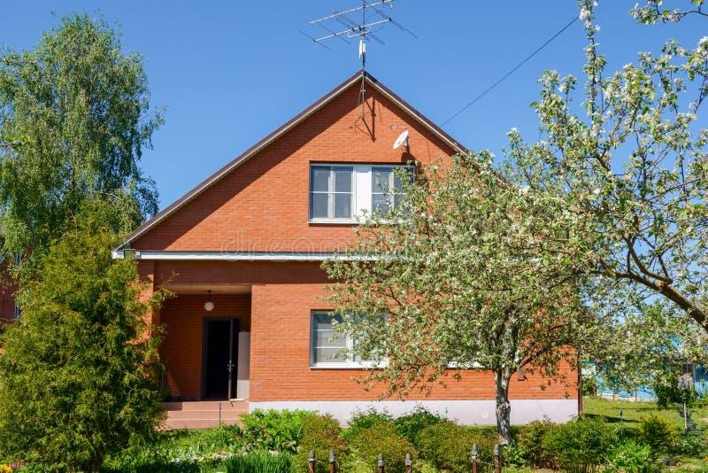 Casa russa rossa con il tetto del metallo ed il recinto del metallo fotografia stock libera da diritti