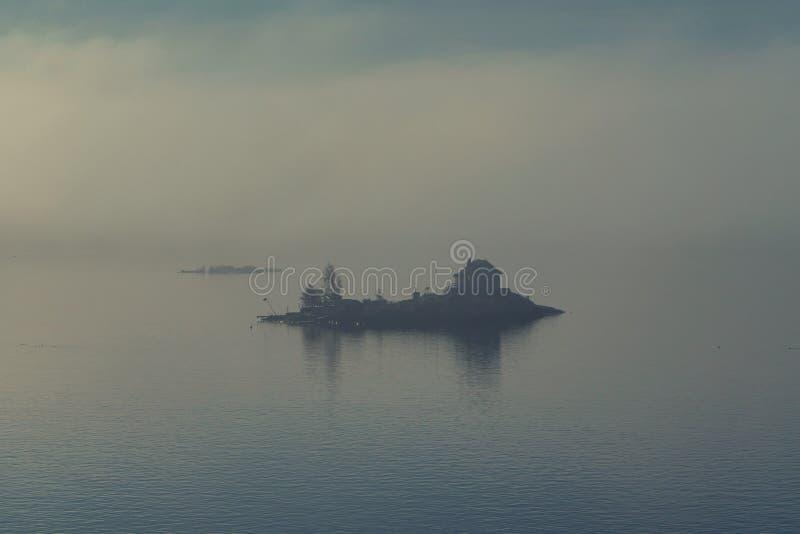 Casa só na ilha pequena na paisagem nevoenta da névoa fotografia de stock