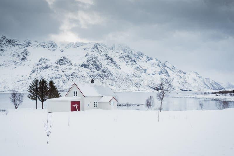 Casa só pelo mar e montanhas no inverno foto de stock