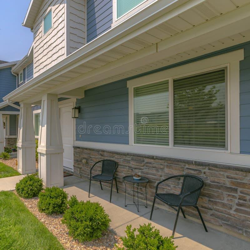 Casa soleggiata con le mobilie sul piccolo portico fotografia stock libera da diritti
