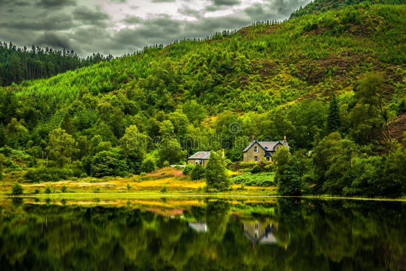 Casa solitaria en la calma y lago liso en Escocia imagen de archivo libre de regalías