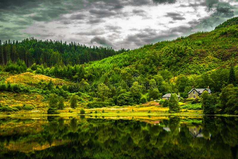Casa solitaria en la calma y lago liso en Escocia imágenes de archivo libres de regalías