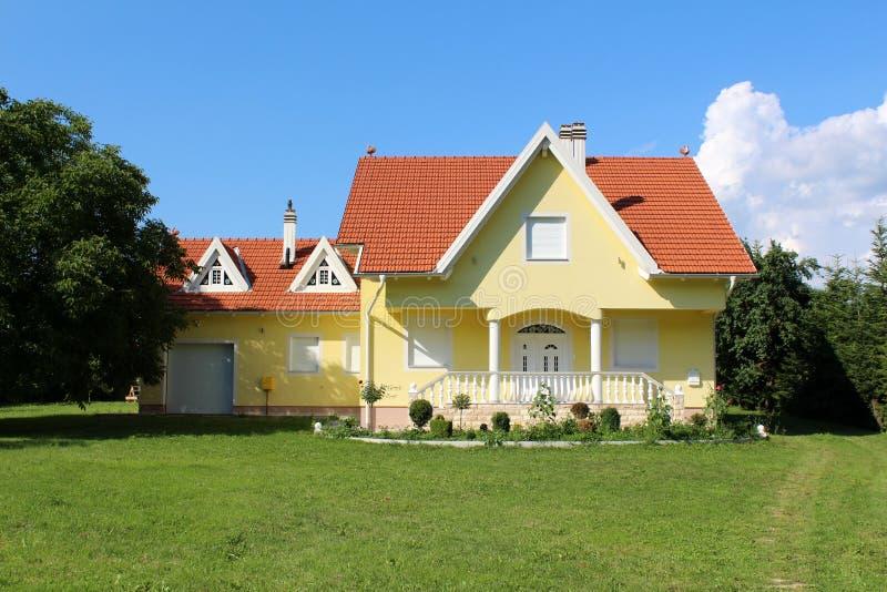 Casa suburbana amarela moderna da família com a garagem pequena ao lado dela foto de stock royalty free