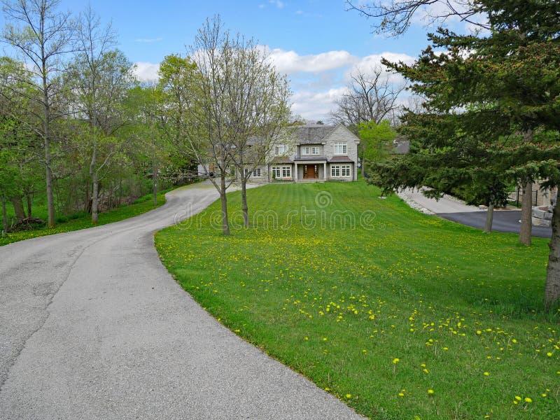 Casa suburbana com a entrada de automóveis muito longa foto de stock royalty free