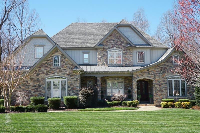 Casa suburbana com exterior de pedra e gramado verde em uma vizinhan?a afluente foto de stock royalty free