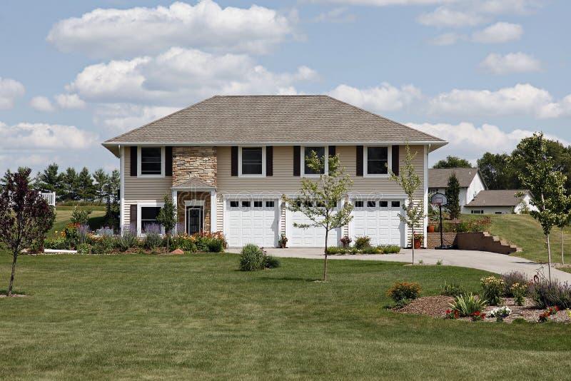 Casa suburbana con un garage delle tre automobili immagini stock