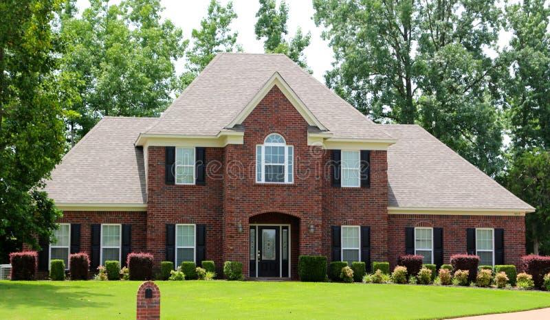 Casa suburbana del ceto medio elegante del mattone rosso immagini stock libere da diritti