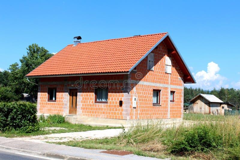 Casa suburbana della famiglia del piccolo mattone non finito con la vecchia tettoia di legno nel fondo fotografia stock