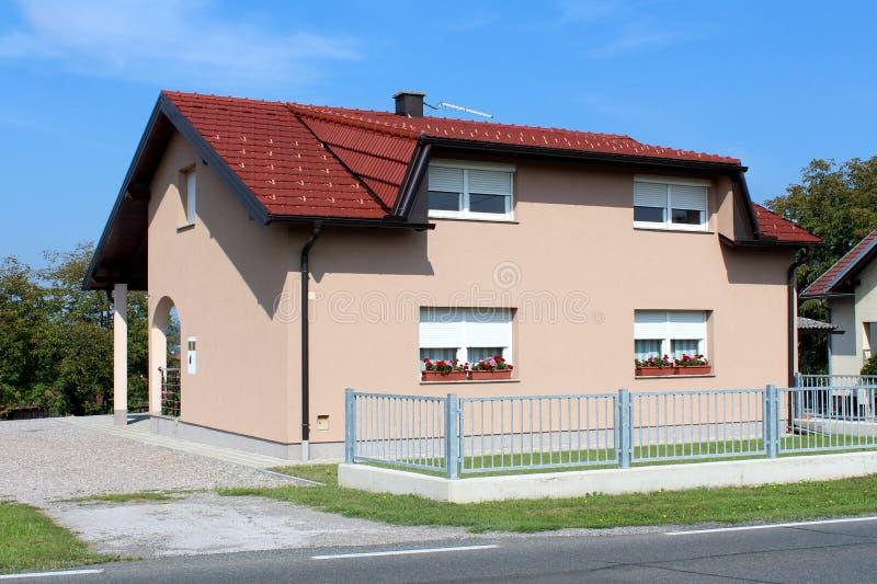 Casa suburbana pequena inteiramente renovada da família cercada com entrada da garagem da cerca e do cascalho do metal fotografia de stock