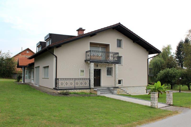 Casa suburbana rinnovata della famiglia con il balcone anteriore e l'entrata di pietra delle mattonelle circondati con erba verde immagine stock