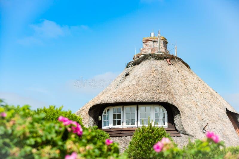 Casa típica con el tejado de la paja en pequeño pueblo en la isla de Sylt, Alemania foto de archivo