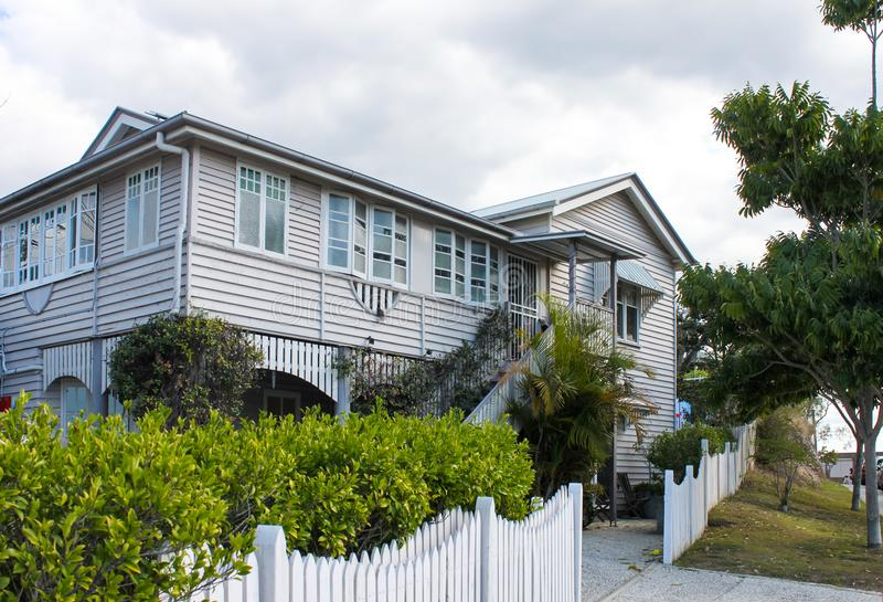 Casa típica de Queensland com folha tropical e cerca de piquete branca no dia nublado em Austrália fotografia de stock