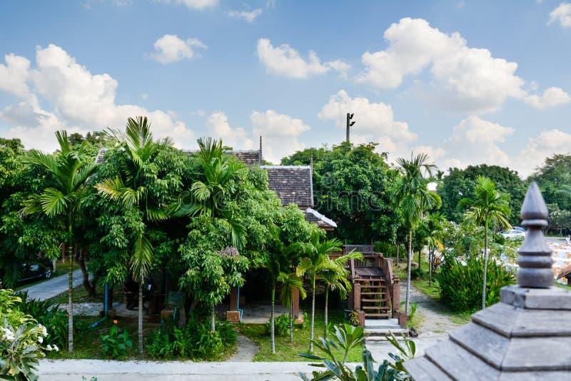 Casa tailandesa del estilo situada entre muchos árboles verdes foto de archivo libre de regalías