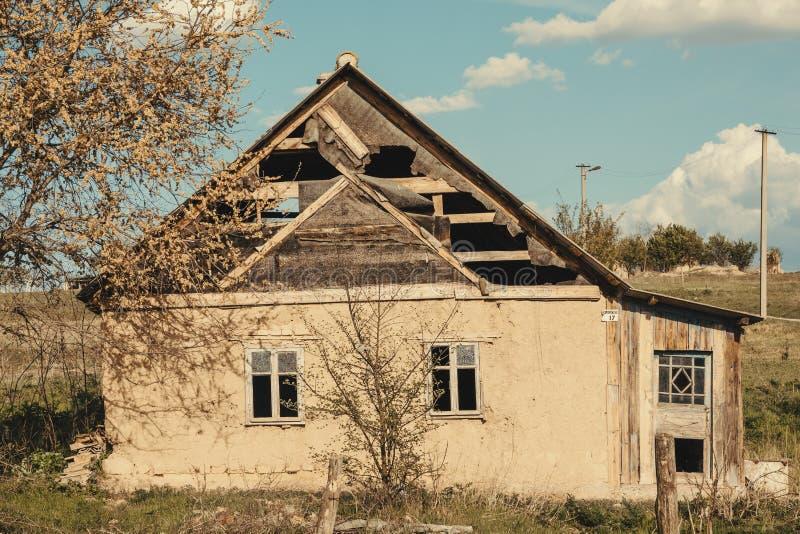 Casa tradicional velha abandonada com uma árvore na parte dianteira em uma vila ucraniana Paredes inclinadas, devasta??o rural imagens de stock royalty free