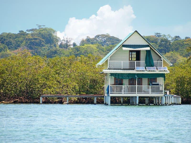 Casa tropicale sopra acqua con i pannelli solari fotografia stock libera da diritti