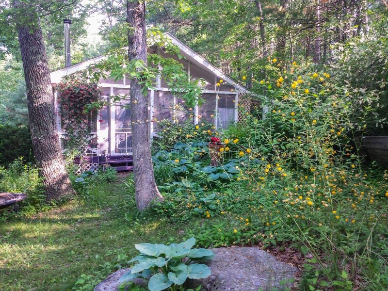 Casa u hogar con el pórtico rodeado por los árboles y los arbustos imagenes de archivo