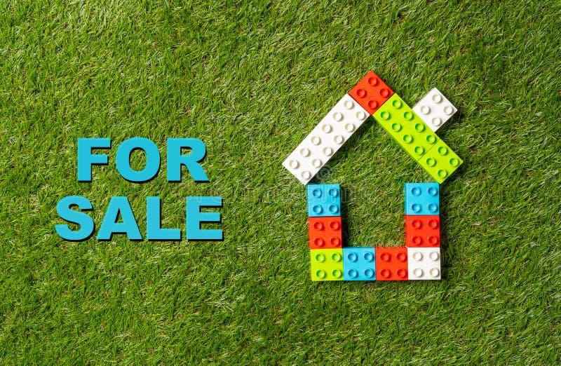 Casa variopinta dei blocchetti del giocattolo e per il testo di vendita scritto su erba verde nell'industria di proprietà di inve fotografie stock libere da diritti