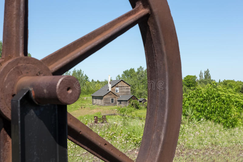 Casa velha vista através de Rusty Wheel imagens de stock