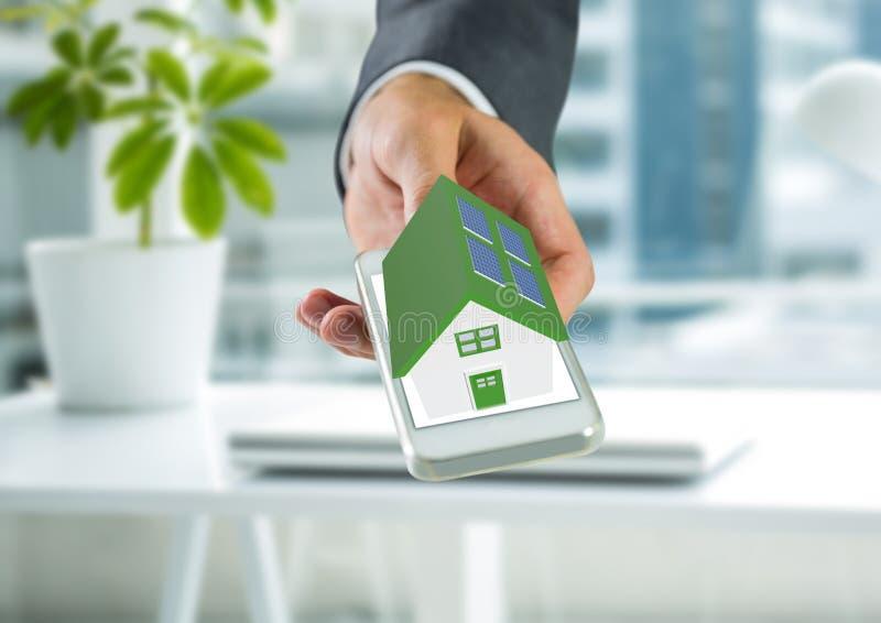 casa verde del panel solar a mano en la oficina imagen de archivo libre de regalías