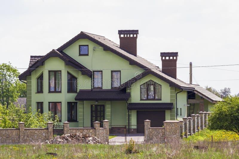 Casa verde lujosa grande hermosa del ladrillo con el garaje, la calzada pavimentada, dos chimeneas, el tejado tejado y la cerca d fotos de archivo libres de regalías